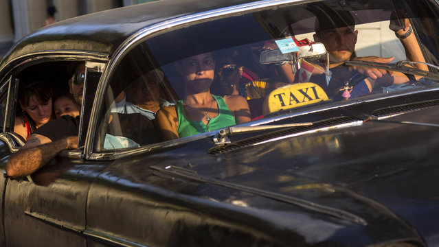 A taxi driver transports a car full of passengers, in Havana, Cuba, Tuesday, February 17, 2015. (Photo by Ramon Espinosa/AP Photo)
