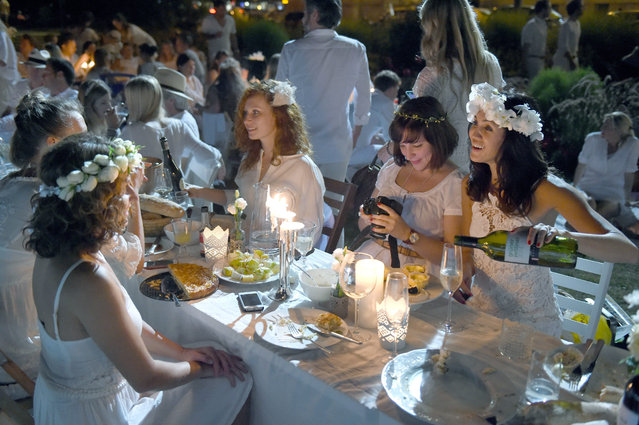 """A picture made available on 06 August shows participants dressed in white attending the event """"Dinner in White"""" at the Old Botanical Garden in Munich, Germany, 05 August 2015. (Photo by Felix Hoerhager/EPA)"""