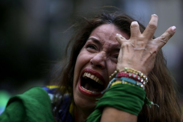 A Brazilian soccer fan cries as she watches her team during a live telecast of the semifinals World Cup soccer match between Brazil and Germany, in Belo Horizonte, Brazil, Tuesday, July 08, 2014. (Photo by Bruno Magalhaes/AP Photo)