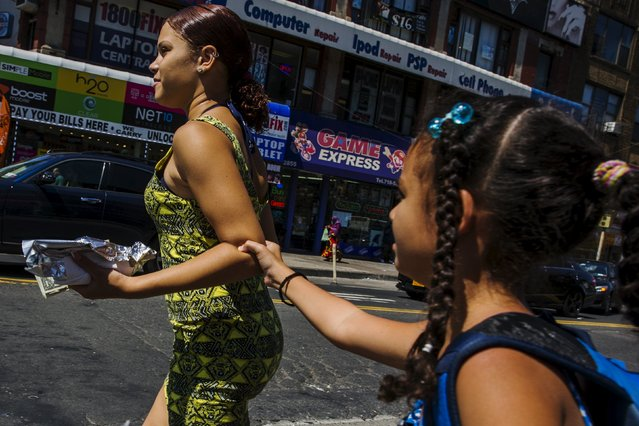 Two young women cross the street in a region of the South Bronx that has seen a deadly outbreak of Legionnaires' disease in New York August 7, 2015. New York Governor Andrew Cuomo will send state health inspectors to New York City on Saturday to help inspect cooling towers in response to a deadly outbreak of Legionnaires' disease, officials said on Friday. (Photo by Lucas Jackson/Reuters)