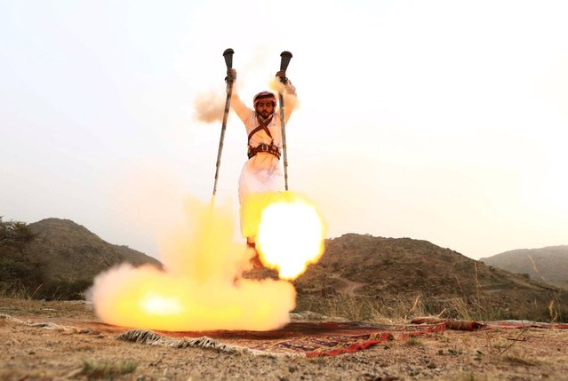 A man fires weapons as he dances during a traditional excursion near the western Saudi city of Taif, August 8, 2015. Saudis usually party in such excursions as they celebrate wedding or graduation. (Photo by Mohamed Al Hwaity/Reuters)