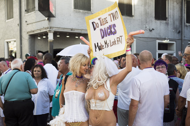 Two women underneath a provocative sign during the Sexual Freedom Parade, part of Naughty in N'awlins held in New Orleans, Louisiana, Wednesday July 5th, 2017. (Photo by Mathew Growcoot/News Dog Media)
