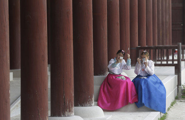 "Women in South Korean traditional ""Hanbok"" attire, fix their make up at the Gyeongbok Palace, the main royal palace during the Joseon Dynasty, in Seoul, South Korea, Monday, June 20, 2016. Wearing a ""Hanbok"", mostly rented, has become a fashionable trend among the youth, commonly seen at palaces and other traditional places. (Photo by Ahn Young-joon/AP Photo)"