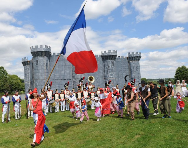 Villagers in revolutionaries' costumes gesture around a wooden and cardboard fortress and take part in the commemorating of the storming of the Bastille during Bastille Day, in Lavaré, western France, on Jule 14, 2014. (Photo by Jean-Francois Monier/AFP Photo)