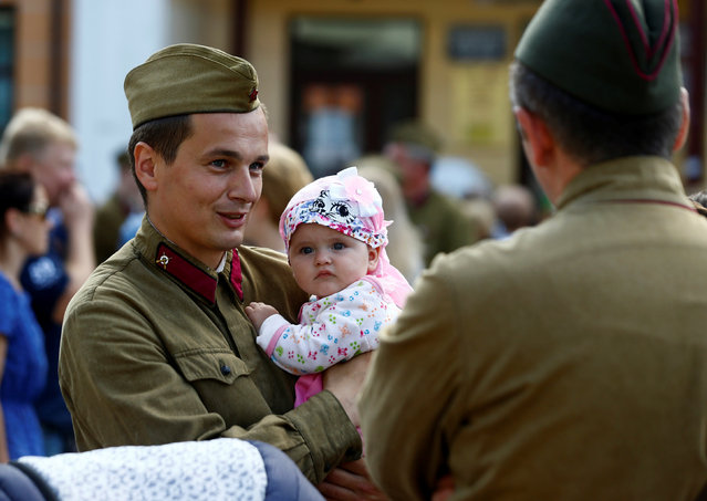 A military enthusiast dressed as  World War Two Red Army soldier holds his child as he marks the 75th anniversary of the Nazi Germany invasion, in Brest, Belarus June 21, 2016. (Photo by Vasily Fedosenko/Reuters)