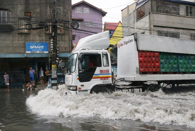 A delivery truck negotiates flooded roads as Typhoon Rammasun batters suburban Navotas, north of Manila, Philippines on Wednesday, July 16, 2014. (Photo by Aaron Favila/AP Photo)