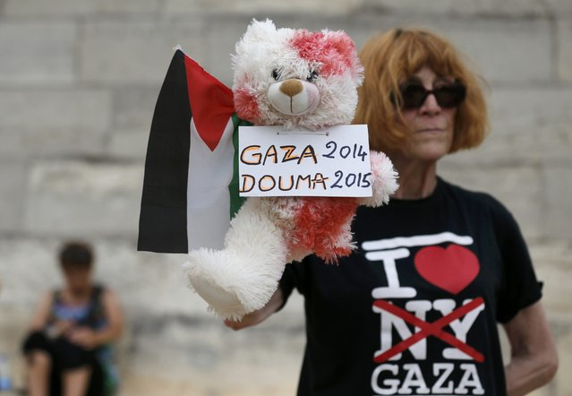 """A woman holds a child's stuffed bear, covered in mock blood, and holding a Palestinian flag to protest the """"Tel Aviv on Seine"""" event on a artificial sand beach at """"Paris Plages"""" in Paris, France, August 13, 2015. (Photo by Pascal Rossignol/Reuters)"""