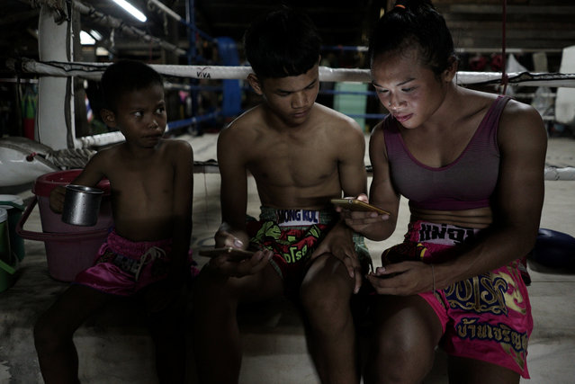 Muay Thai boxer Nong Rose Baan Charoensuk (R), 21, who is transgender, spends time with her friend after a training session at a gym in Buriram province, Thailand, July 3, 2017. (Photo by Athit Perawongmetha/Reuters)