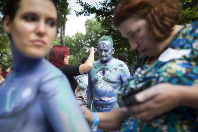 Jack van Riper, of New Jersey, is painted at Columbus Circle as body-painting artists gathered to decorate nude models as part of an event featuring artist Andy Golub, Saturday, July 26, 2014, in New York. Golub's event Saturday included a post-painting march down Broadway and a return to Times Square for a photo shoot. (Photo by John Minchillo/AP Photo)