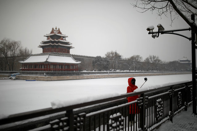 A woman wearing a face mask takes selfies after snowfall outside the Forbidden City, as the country is hit by an outbreak of the new coronavirus, in Beijing, China on February 6, 2020. (Photo by Carlos Garcia Rawlins/Reuters)