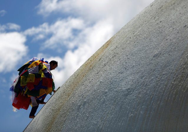 A man carries prayer flags offered by the devotees as he climbs to hang them from the Boudhanath Stupa, a UNESCO world heritage site famous among tourists, in Kathmandu, Nepal August 2, 2017. (Photo by Navesh Chitrakar/Reuters)