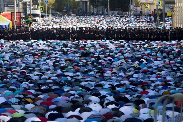 Muslim men, bowing toward Mecca, offer Eid al-Fitr prayers that marks the end of the holy fasting month of Ramadan as police guard them at the main mosque in Moscow, Russia, Monday, July 28, 2014. More than two hundred thousand Muslims gathered at Moscow's mosques to celebrate the Eid al-Fitr. (Photo by Evgeny Feldman/AP Photo)