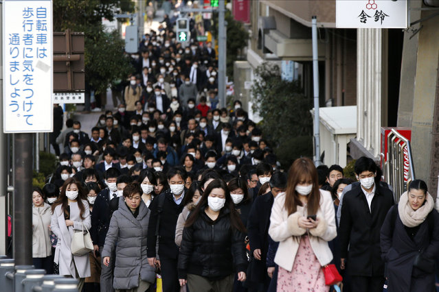 People wear masks as they commute during the morning rush hour Thursday, February 20, 2020, in Chuo district in Tokyo. A test event for the Tokyo Olympics scheduled for later this month that would have involved some non-Japanese athletes is being rejiggered because of fear of the spreading virus from China. It will now involve only Japanese athletes. (Photo by Kiichiro Sato/AP Photo)