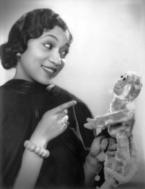 1933: British singer and actress Elizabeth Welch playfully admonishes a toy monkey