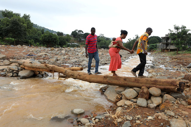 A man helps a woman cross a log bridge after the flash flood washed away a concrete bridge at Pentagon, in Freetown August 18, 2017. (Photo by Afolabi Sotunde/Reuters)