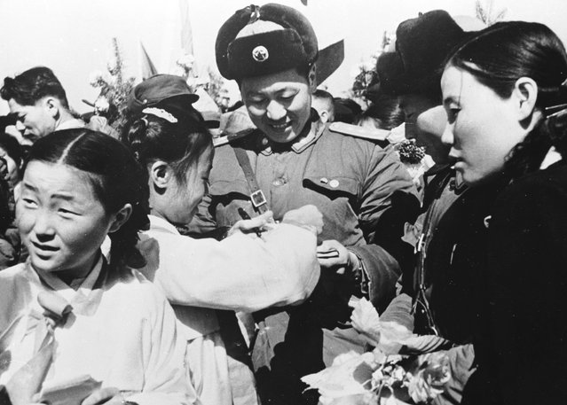 Korean girls present a member of the Chinese People's Volunteer Army with a bouquet of flowers prior to the mass withdrawal of Chinese troops from North Korea, 29th March 1958. (Photo by Keystone)
