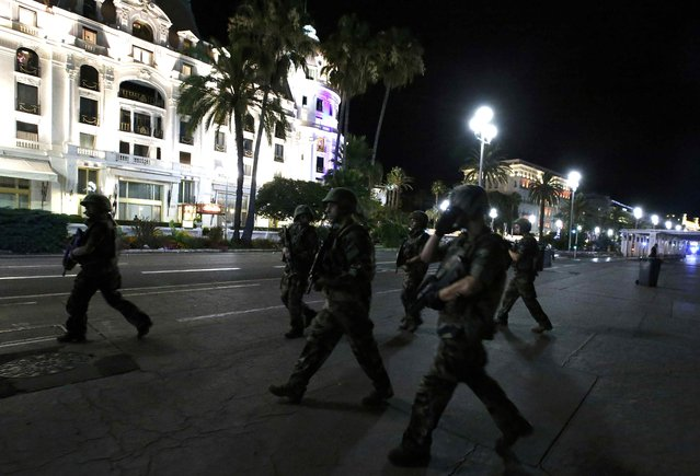 French soldiers advance on the street after at least 30 people were killed in Nice, France, when a truck ran into a crowd celebrating the Bastille Day national holiday July 14, 2016. (Photo by Eric Gaillard/Reuters)