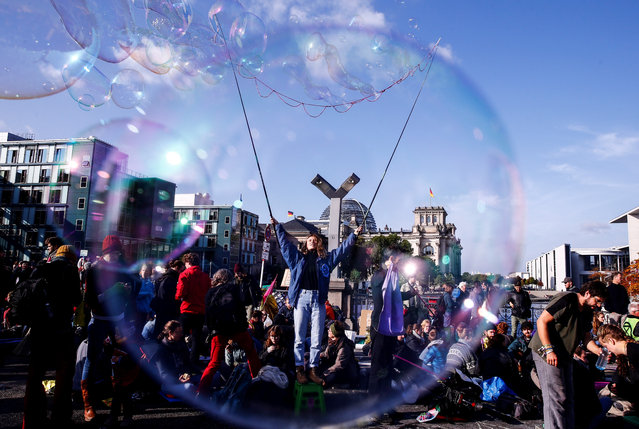 A member of Extinction Rebellion, a group of environmentalist activists, makes bubbles as protests continue in order to draw attention to climate change and global warming in Berlin, on October 9, 2019. Extinction Rebellion activists began gathering in cities around the world on October 7 to kick off a fortnight of global civil disobedience demanding governments take urgent action on climate change. Protesters gathered at various points of the city and blocked traffic at Marshall-Bridge. (Photo by Abdulhamid Hosbas/Anadolu Agency via Getty Images)
