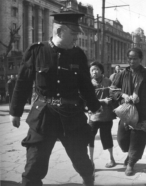 1948年3月,外滩。警察逮捕拿棉花的母女。 (In March 1948, the Bund. Arrested by the police to take the cotton mother and daughter)
