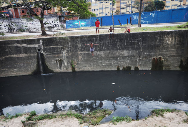 A teen jumps into a polluted canal on July 16, 2016 in Rio de Janeiro, Brazil. The canal receives untreated sewage and is one of many polluted waterways in the city. Teens sometimes jump into the canal to cool off or for fun. (Photo by Mario Tama/Getty Images)