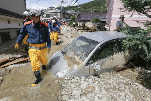 Rescue workers walk pass a damaged car as they arrive for shift change at a landslide site in Hiroshima, Hiroshima Prefecture, western Japan, 21 August 2014. About 2,500 rescuers searched for survivors a day after landslides killed 39 people in western Japan following torrential rain, a report said. (Photo by Kimimasa Mayama/EPA)