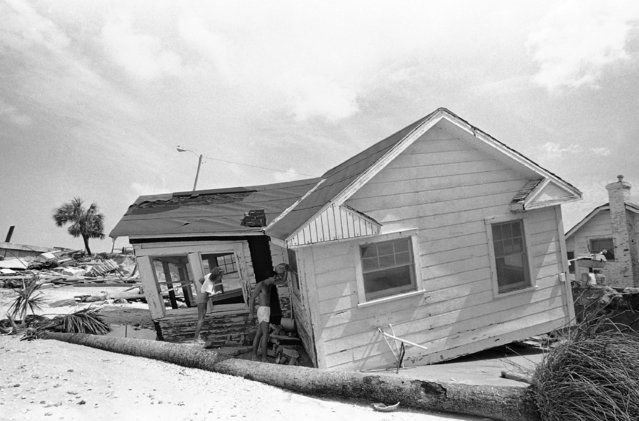 Residents of Indian Rocks Beach, Fla., look inside a damaged house on September 3, 1985. They were allowed to return to their house to inspect the damage. (Photo by Raul de Molina/AP Photo)