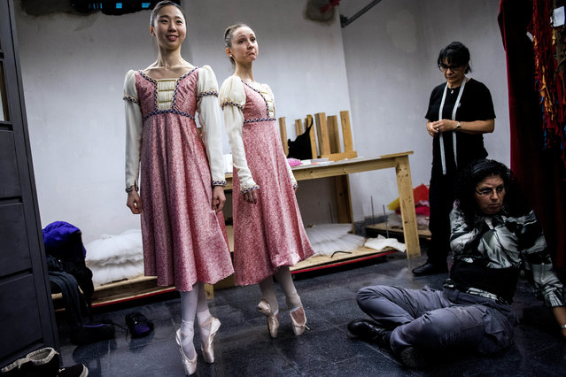 In this Wednesday, September 6, 2017 photo, ballet dancers Eunsil Kim, left, and Paula Penachio try on their dresses at the costume workshop at the Adela Reta Auditorium in Montevideo, Uruguay. The building also has a carpentry workshop where the set designs are built for performances, which now often sell out. (Photo by Matilde Campodonico/AP Photo)
