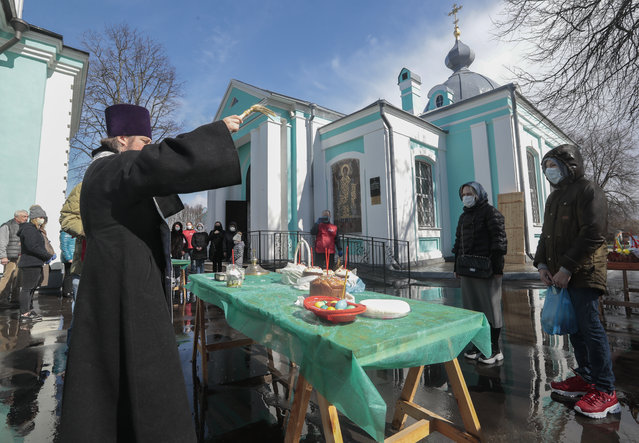 Russian Orthodox Church priest blesses food on the eve of Orthodox Easter Sunday in Moscow, Russia, 18 April 2020. Patriarch of Moscow and All Russia called believers to watch Easter service on TV and not to visit the churches in order to avoid coronavirus infection spreading. (Photo by Sergei Chirikov/EPA/EFE)