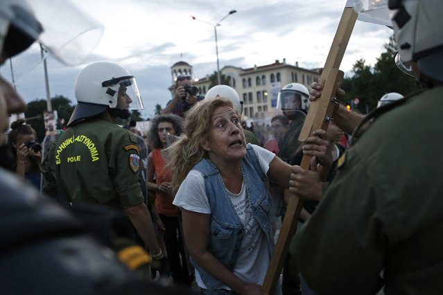A protester argues with a police officer during a rally against austerity measures in the city of Thessaloniki September 6, 2014. Greek Prime Minister Antonis Samaras on Saturday announced cuts to unpopular taxes introduced at the height of the country's debt crisis, in a bid to show the nation that over four years of austerity are finally nearing an end. (Photo by Alkis Konstantinidis/Reuters)