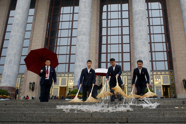 Security officers clean the steps outside the Great Hall of the People before the opening of the 19th National Congress of the Communist Party of China in Beijing, China October 18, 2017. (Photo by Thomas Peter/Reuters)