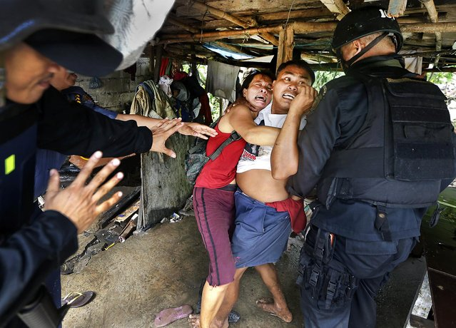 Philippine National Police try to arrest resisting settlers during the demolition of their shanty in Taguig City, on September 20, 2012. The informal settlers' community of mostly retired police and military personnel was demolished to pave the way for new development projects. (Photo by Bullit Marquez/Associated Press)