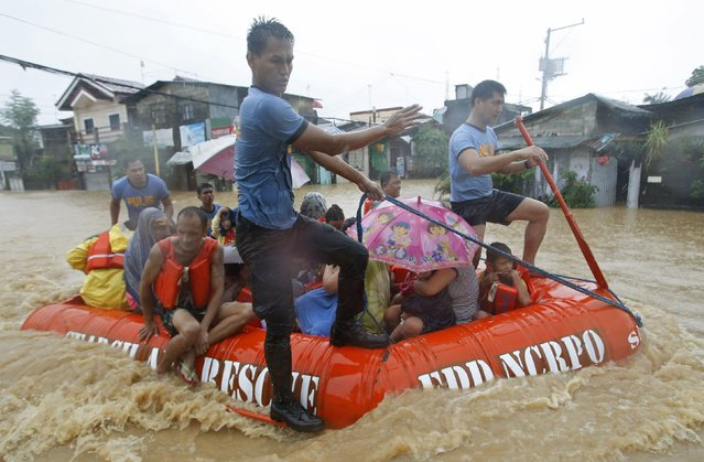 Flood victims  are evacuated in a rescue boat after their homes were swamped by heavy flooding in Marikina, Metro Manila September 19, 2014. (Photo by Erik De Castro/Reuters)