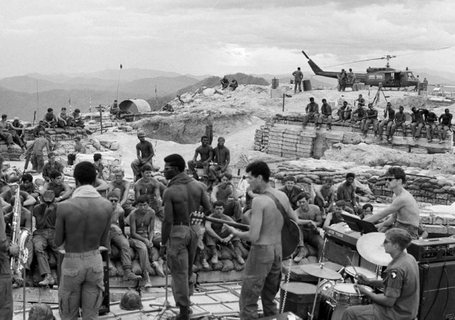 GIs of Firebase Catherine, the Third Brigade of the U.S. 101st Division, go into a rock session as they are surrounded by symbols of the war – wooden bunkers, helicopter and sandbags – in South Vietnam, July 21, 1970.  They are dug in on a hill south of the demilitarized zone in the northernmost portion of the country. (Photo by Giancarlo Meyer/AP Photo)
