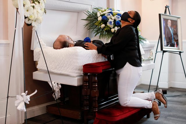Maria Ortiz reacts while kneeling beside the body of her partner Jose Holguin, 50, originally from the Dominican Republic and who died of complications related to the coronavirus disease (COVID-19), during a viewing service for Mr. Holguin at International Funeral & Cremation Services in the Harlem neighborhood of Manhattan, New York City, U.S., May 16, 2020. (Photo by Andrew Kelly/Reuters)