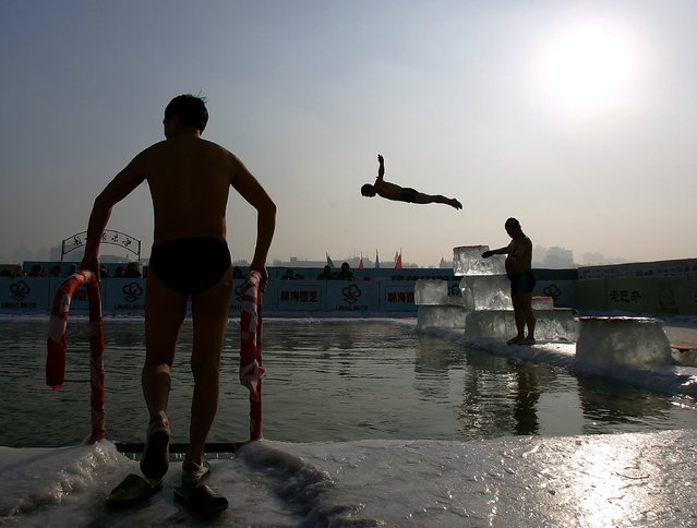 A winter swimming performer dives into a pool carved out of the frozen Songhua river during the 22nd Harbin International Ice and Snow Festival on January 11, 2006 in Harbin, Heilongjiang Province in north China. Harbin is one of China's coldest cities and each winter hosts an ice festival, with famous buildings and landmarks from around the world recreated in ice. (Photo by Cancan Chu)