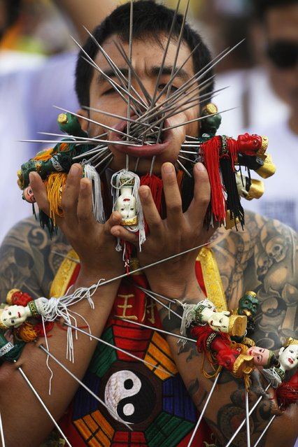 A devotee of the Chinese Bang Neow Shrine with many spikes pierced through his cheeks and skin, takes part in a street procession celebrating the annual vegetarian festival in Phuket September 29, 2014. (Photo by Damir Sagolj/Reuters)