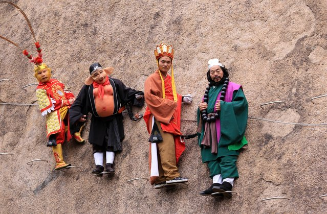 People in fancy dress costume dangling from a cliff face pose for photos at the Chaya Mountain scenic spot on November 11, 2017 in Zhumadian, Henan Province of China. (Photo by VCG/VCG via Getty Images)