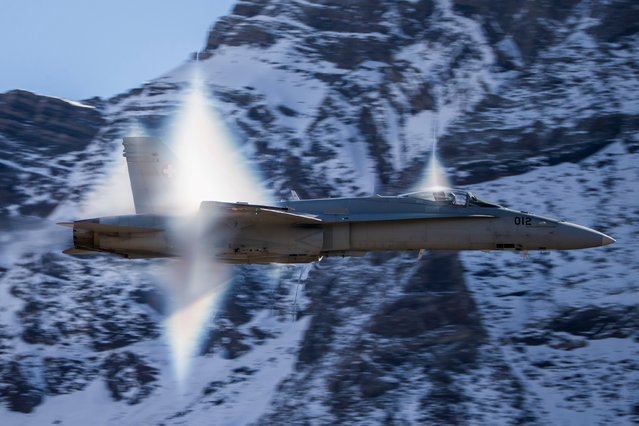 In this October 10, 2017 photo a F/A-18 Hornet of the Swiss Air Force performs a highspeed fly and makes the sonic barrier visible when the Swiss Air Force pilots show their skills in the Swiss Alps above Axalp Ebenfluh. At an altitude of 2,200 m above sea level, spectators could marvel at a unique aviation display performed at the highest air force firing range in Europe. (Photo by Christian Merz/Keystone via AP Photo)