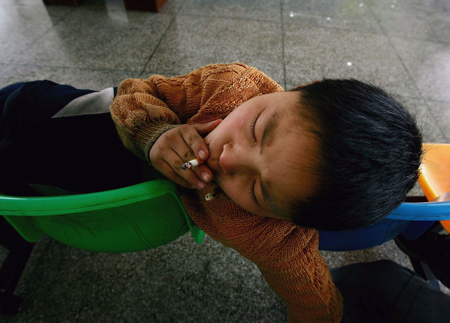 A kid from Sichuan provice smokes at an assistance center February 23, 2005 in Shenzhen, Guangdong Province, China. (Photo by Cancan Chu/Getty Images)