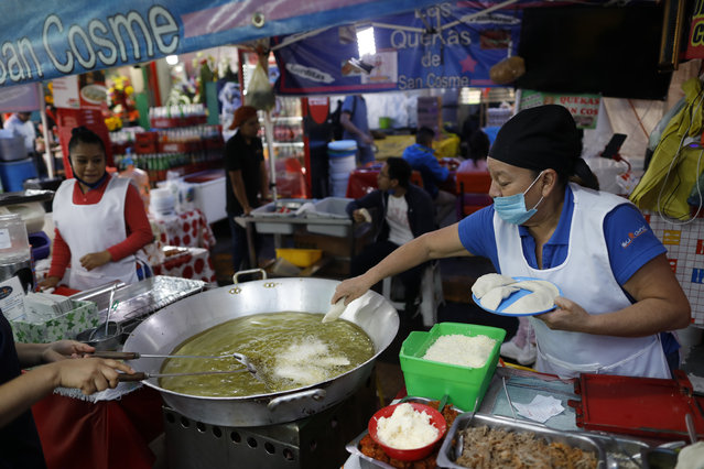 """Sabina Hernandez Bautista, 59, prepares food in a stall inside Mercado San Cosme, where some vendors have put in place their own protective measures against coronavirus while others continue to work without masks or barriers, in Mexico City, Thursday, June 25, 2020. """"We are all afraid"""", said Bautista, who added she had no choice but to work to be able to feed her family, including her daughter who is attending university. (Photo by Rebecca Blackwell/AP Photo)"""