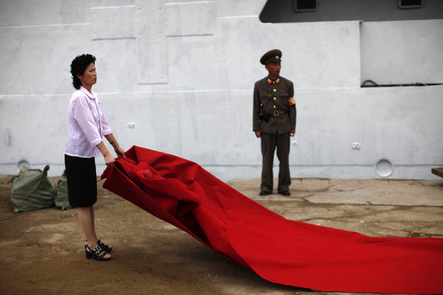 A woman prepares a red carpet for the departure ceremony of Mangyongbyong cruise ship in the North Korean Special Economic Zone of Rason City, northeast of Pyongyang, August 30, 2011. (Photo by Carlos Barria/Reuters)