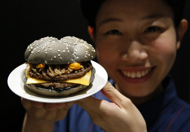 An employee of McDonald's Japan poses with the Ikasumi (squid ink) burger at one of its fast-food outlets in Tokyo October 8, 2014. McDonald's Japan has launched the Halloween-themed black burger, which have buns made from a flour mix of bamboo charcoal powder and black sesame to create the charred look, and beef patties marinated with squid ink sauce. The burger is priced at 370 yen ($3.40) each. (Photo by Toru Hanai/Reuters)