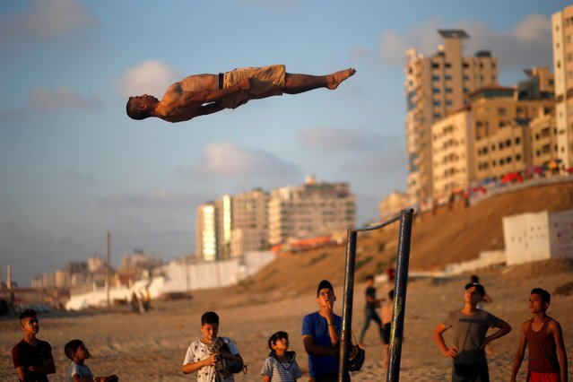 A Palestinian man demonstrates his parkour skills on a beach as the coronavirus disease (COVID-19) restrictions ease in Gaza City on July 10, 2020. (Photo by Mohammed Salem/Reuters)