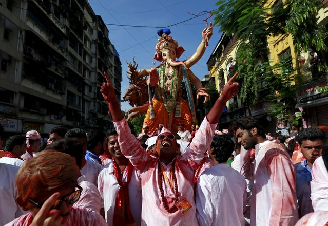 Devotees dance as they pull an idol of Hindu god Ganesh, the deity of prosperity, through a street on the last day of the ten-day-long Ganesh Chaturthi festival in Mumbai, India, September 27, 2015. (Photo by Danish Siddiqui/Reuters)