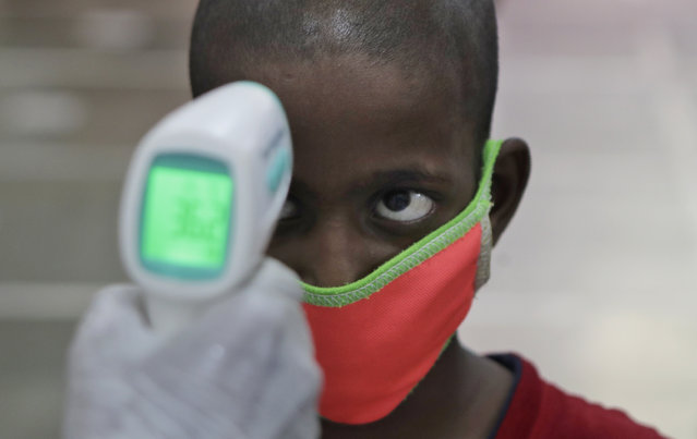 A health worker checks the body temperature of a boy at a medical camp to screen residents for COVID-19 symptoms in Mumbai, India, Friday, July 17, 2020. India crossed 1 million coronavirus cases on Friday, third only to the United States and Brazil, prompting concerns about its readiness to confront an inevitable surge that could overwhelm hospitals and test the country's feeble health care system. (Photo by Rajanish Kakade/AP Photo)