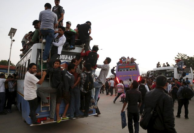 Passengers take a ride on an overcrowded bus as limited public transportation operates in the city during the ongoing crisis on oil and fuel in Kathmandu, Nepal September 29, 2015. Tension between Nepal and India has spiked since Nepal adopted a new constitution last week, upsetting southern minority groups who fear being marginalised in a new federal structure. (Photo by Navesh Chitrakar/Reuters)