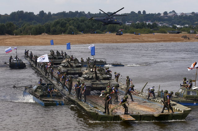 Members of the Russian team transport tanks on a pontoon bridge during the Open Water competition for pontoon bridge units as part of the International Army Games-2015 in the town of Murom, Russia, August 8, 2015. (Photo by Maxim Zmeyev/Reuters)