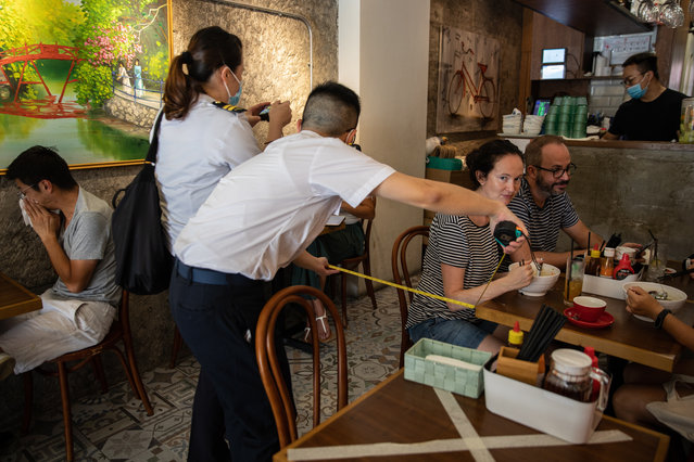 Officers with the Food and Environmental Hygiene Department measure the distance between tables in a restaurant in Hong Kong, China, 16 July 2020. According to guidelines by the government, tables within any catering premises must be arranged in a way to ensure there is a distance of at least 1.5 metres between one table and another table at the premises. Hong Kong Health authorities have been reporting dozens of local coronavirus disease (COVID-19) cases daily over the last four days. (Photo by Jerome Favre/EPA/EFE)