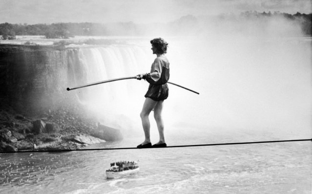 French high wire artist Philippe Petit walks across a tightrope that is 45 feet out over the Niagara River. The Horseshoe Falls are seen in the background and a 'Maid of the Mist' tour boat is seen below. October 5, 1986. (Photo by James P. McCoy/AP Photo)