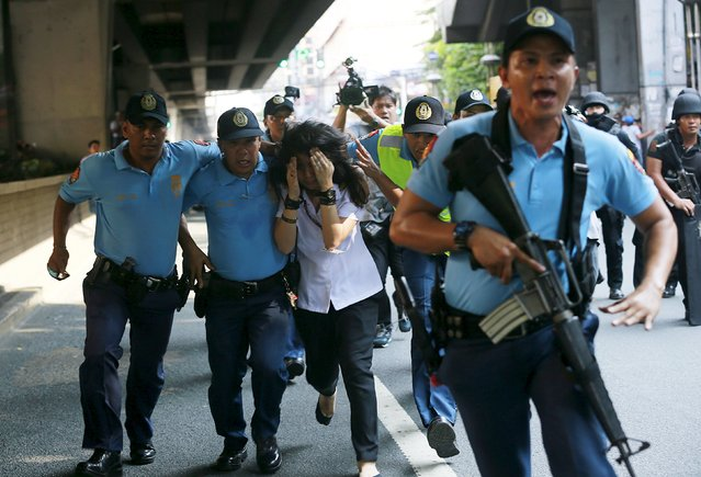 Policemen assist one of the passengers to safety during a robbery incident inside a public bus in Manila October 8, 2015. Policemen killed the suspected robber after he took a student hostage inside a public bus that was passing through an avenue in Manila, local media reported. (Photo by Romeo Ranoco/Reuters)